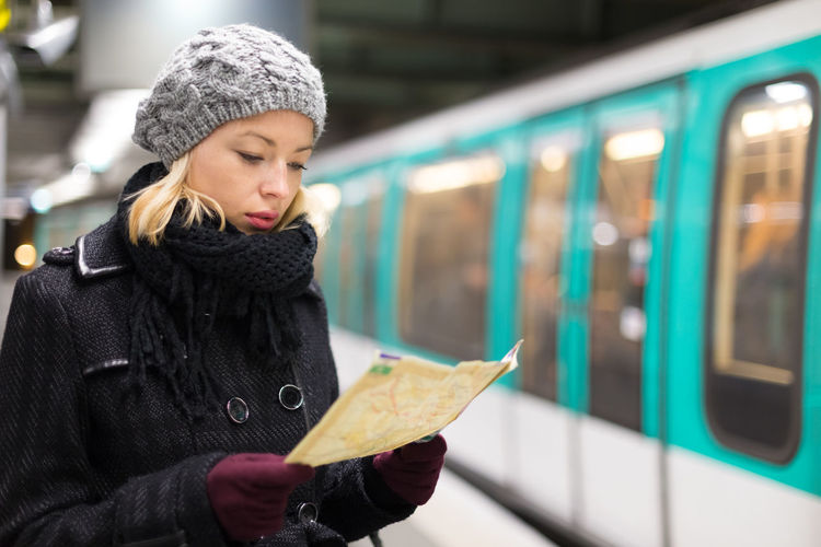 Young woman holding umbrella in train during winter