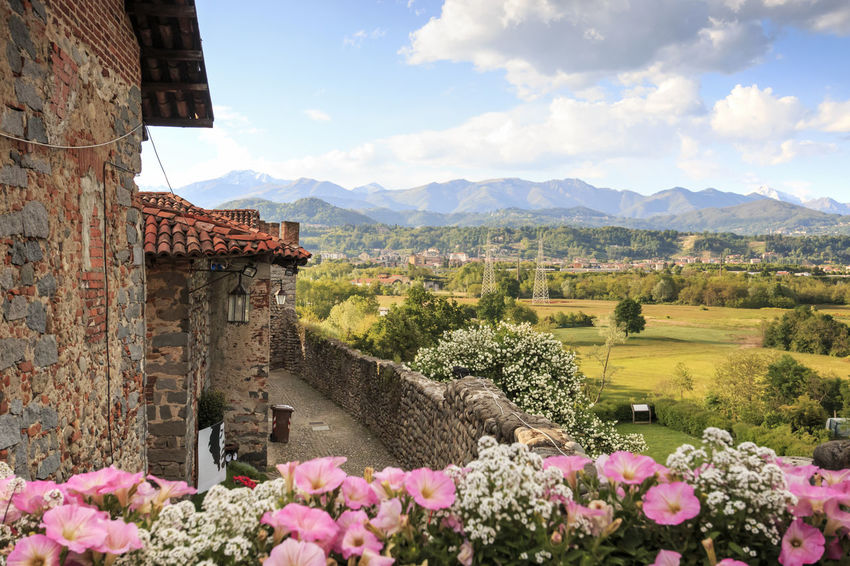 Candelo, Biella - May 4, 2016: View form the inside of the Medieval village of Ricetto di Candelo in Piedmont, used as a refuge in times of attack during the Middle Age. Architecture Beauty In Nature Biella Built Structure Candelo Candelo In Fiore Day Flower Growth Hill Italy Landscape Medieval Village Mountain Mountain Range Nature No People Outdoors Plant Ricetto Di Candelo  Scenics Sky Tranquil Scene Tranquility Village