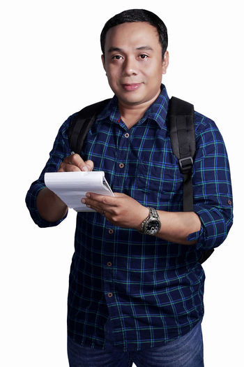 Casual Clothing Communication Front View Holding Human Hand Lifestyles One Person Portrait Real People Smiling Standing Studio Shot Technology Telecommunications Equipment White Background Wireless Technology Young Adult
