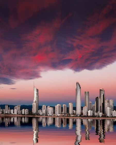 Reflection of buildings in sea against sky during sunset