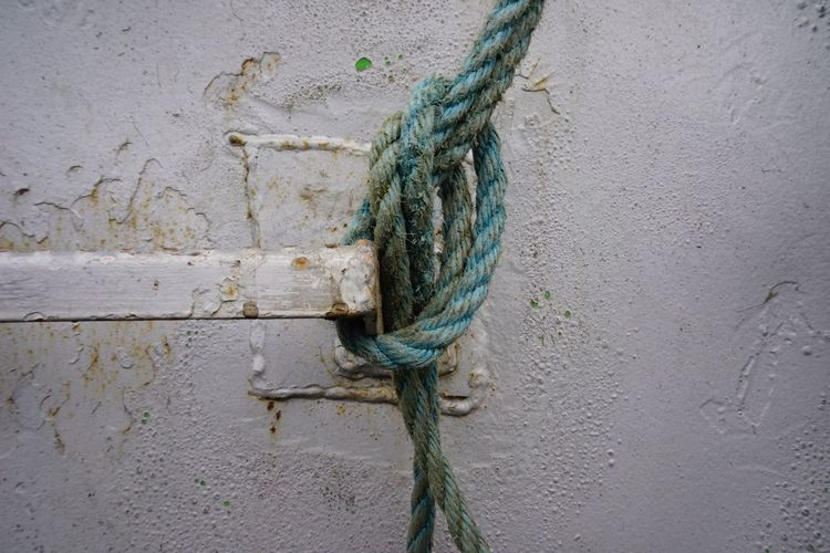 Close-up Of Rope Tied On Metal By Wall