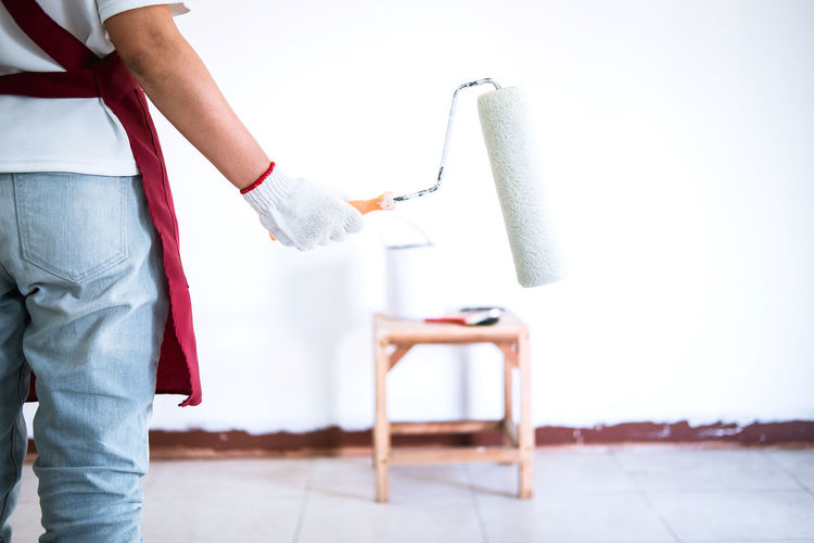 Midsection of painters holding paint roller and container while painting wall at home