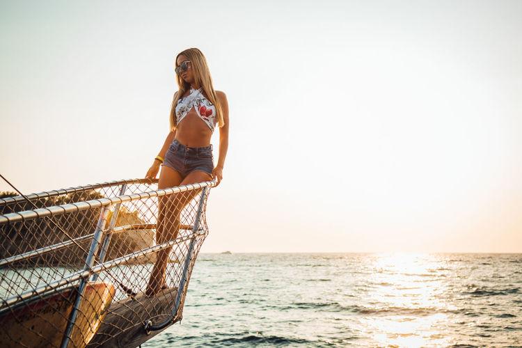 Woman on sea against clear sky