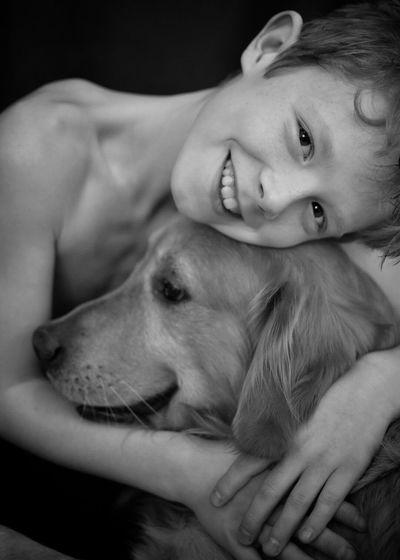 Portrait Of Happy Shirtless Boy Embracing Golden Retriever