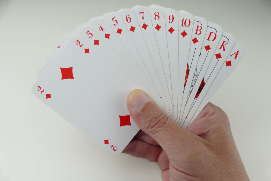 Adult Cards Close-up Day Gambling Gambling Chip Game Cards Holding Human Body Part Human Finger Human Hand Indoors  Karo Karten Kartenspiel Leisure Activity Leisure Games Lifestyles Luck One Person People Playing Poker - Card Game Real People Red