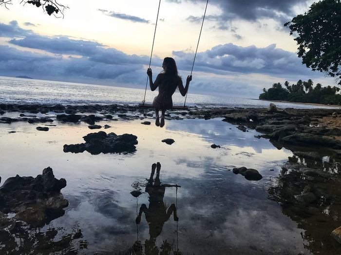 Rear view of silhouette woman swinging at beach during sunset