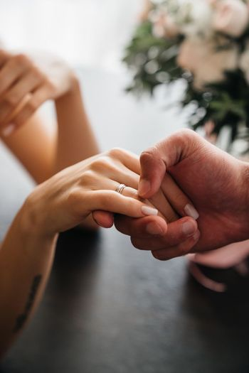 Cropped couple holding hands on table