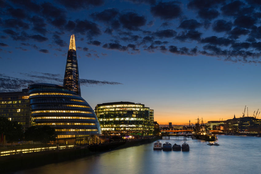Dusk settles over London after sunset along the River Thames and downtown. Architecture Building Exterior Built Structure City Cityscape Development Dusk Glowing Growth Illuminated Modern Nautical Vessel Night Office Building River Sky Skyscraper Tall - High Tower Transportation Travel Travel Destinations Urban Skyline Water Waterfront