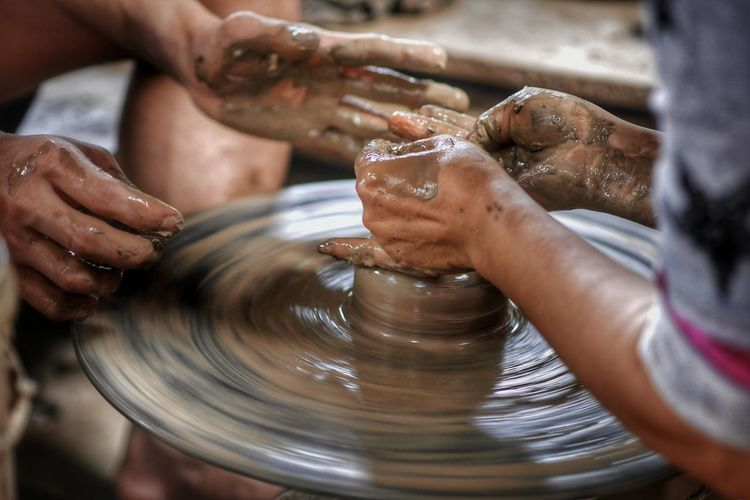 Cropped hands of potters making earthenware on pottery wheel