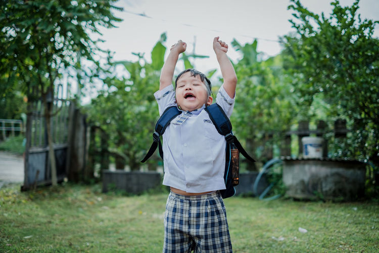 Happy children go back to school.Asian smiling boy going to school for the first time. ASIA Asian  Back Background Backpack Bag Beginning Book Boy Business Caucasian Cheerful Child Childhood Classroom Concept Copy Space Cute Education Elementary Face Fingers First Gesture Graduation Hand Happy Jumping Kid Knowledge Learn Little Little Boy Male One Person People Portrait Preschool Pupil School Showing Sign Smart Smiling Student Success Teenager Two Fingers Uniform Young