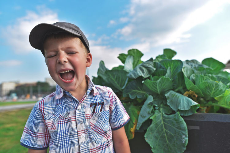 Boy shouting while standing by plants on field