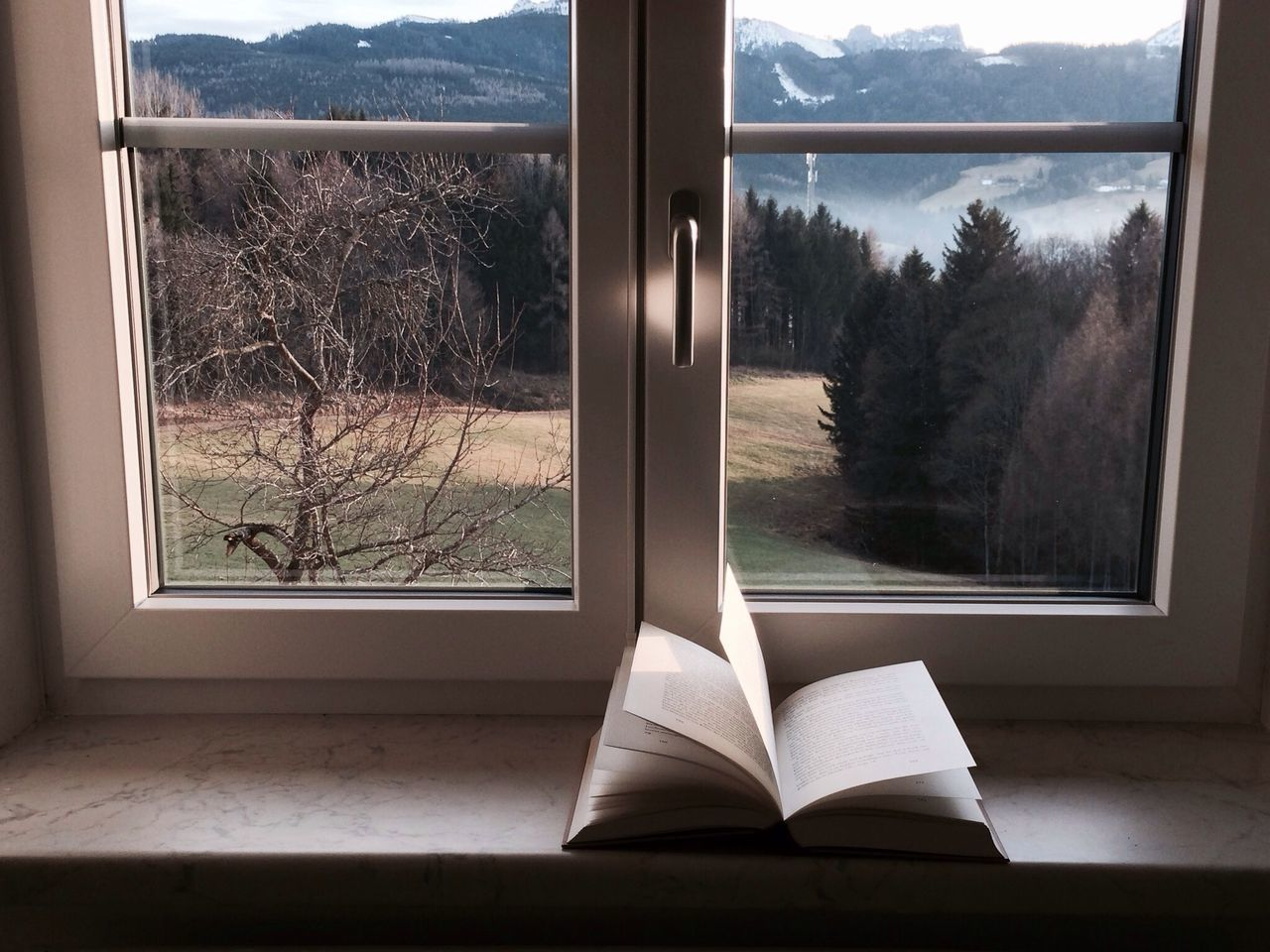 Book on window sill in front of scenic view of mountain through window
