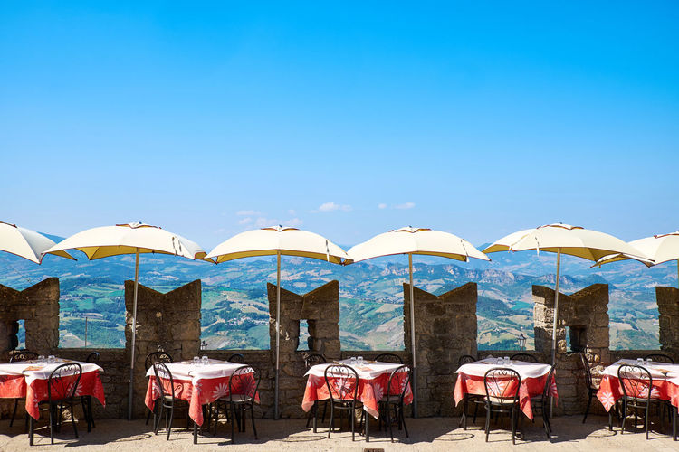 Tables and chairs with parasols arranged against blue sky during sunny day