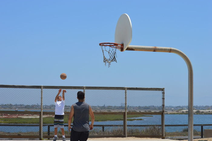 Adult Basketball - Sport Basketball Hoop Basketball Player Clear Sky Court Day Leisure Activity Men One Person Outdoors People Playing Practicing Real People Sky Sport Team Sport