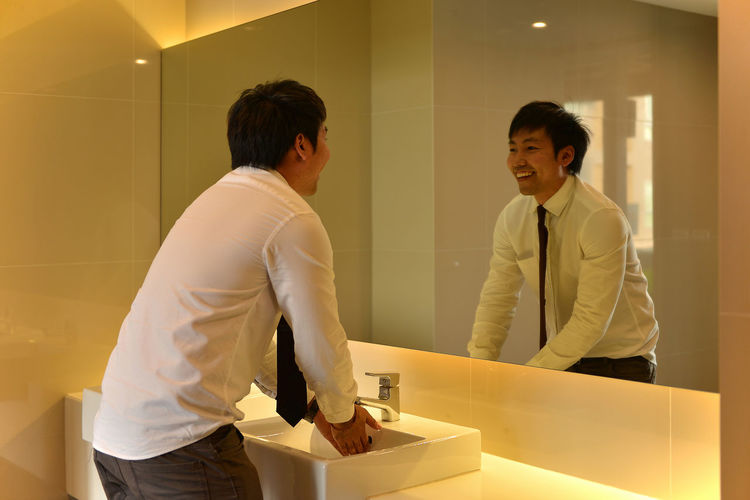 Smiling businessman washing hands in bathroom