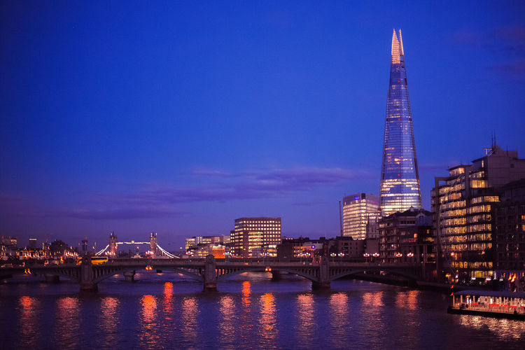 Low angle view of Shard London Bridge by Thames River in city against sky