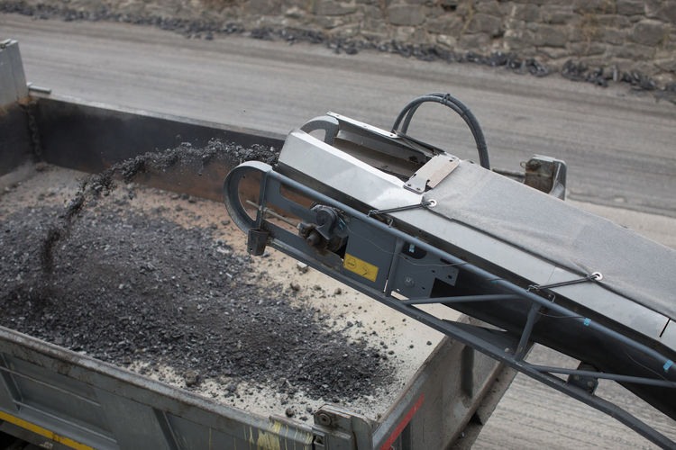 High angle view of conveyor belt by truck at road construction