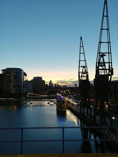 Bridge over river in city against clear sky during sunset