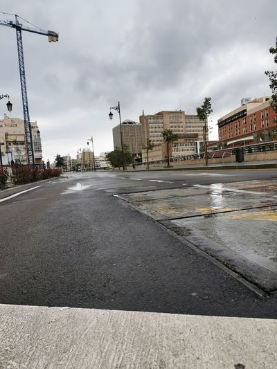 Surface level of wet road against buildings in city