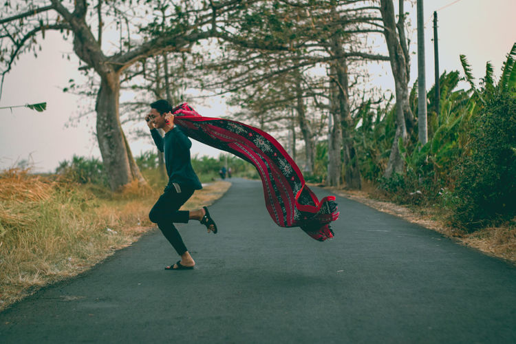 Side view of man holding scarf jumping on road in forest