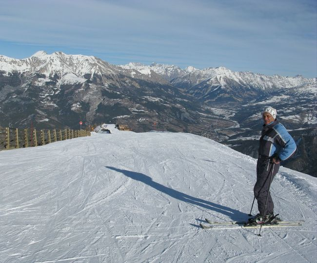 Full length of mature man skiing on snowcapped mountain against sky