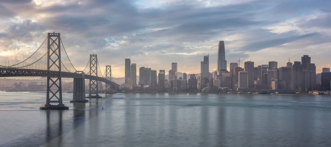 View of bay bridge over sea and buildings against sky san francisco