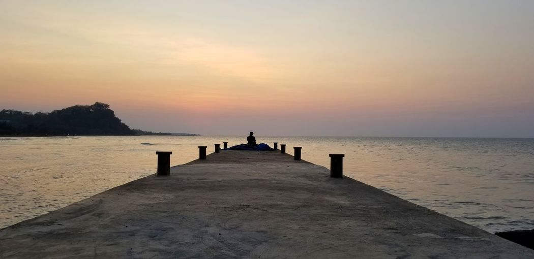 Man On Pier By Sea Against Sky During Sunset
