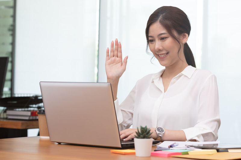 Cheerful businesswoman talking on video call at office