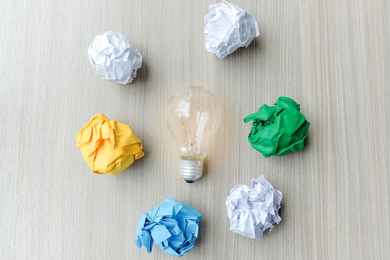 High angle view of light bulb amidst crumpled paper balls on table