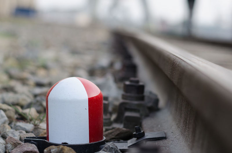 Close-up of signal by railroad tracks