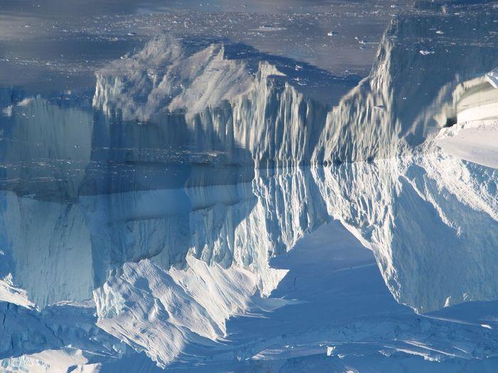 Upside down image of glaciers reflecting on sea