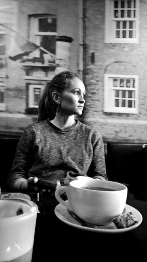 Thoughtful Young Woman Sitting In Front Of Tea On Restaurant Table