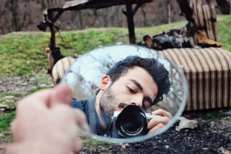 Reflection of teenage boy photographing outdoors