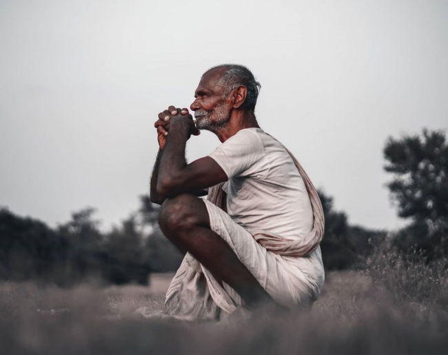 Side view of man sitting on field against sky