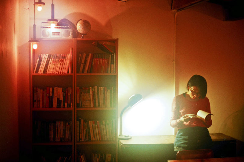 Young woman reading book in illuminated home