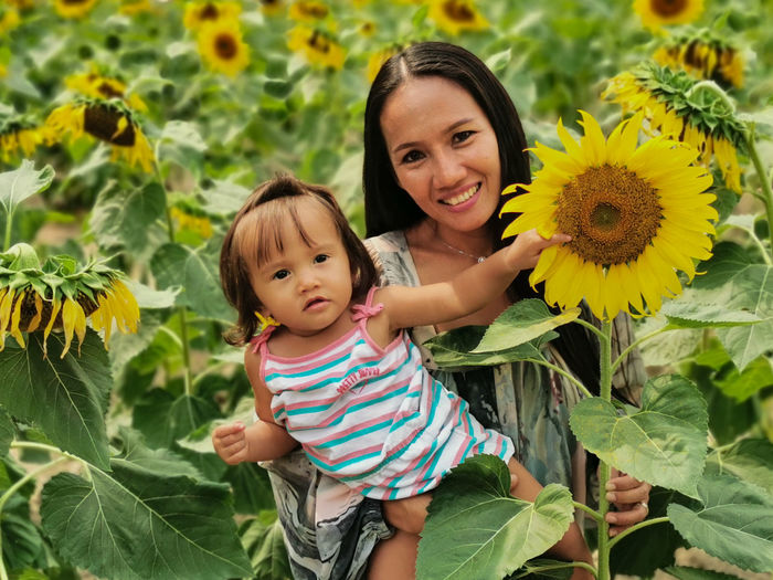 Portrait of a smiling woman with young daughter in yellow sunflower field