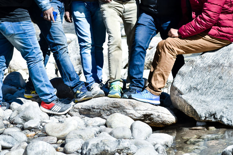 Low section of people sitting on rock