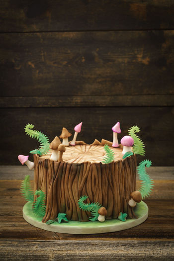 Enchanted forest woodland themed fondant cake with a tree trunk, ferns, mushrooms and leaves on wooden background with copyspace Birthday Cake Fondant Cake Tree Tree Trunk WoodLand Animal Cake Celebration Character Fern Figurine  Fondant  Food Food And Drink Forest Guitar Kid Mushroom Owl Still Life Sugar Arts Sweet Food Theme