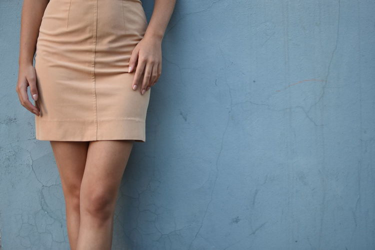 Low section of woman standing against wall