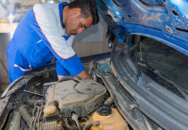 Auto Mechanic Auto Repair Shop Automobile Industry Car Coveralls Engine Examining Industry Land Vehicle Machinery Mechanic Men Mid Adult Mid Adult Men Mode Of Transport Occupation One Man Only One Person Only Men Real People Repairing Transportation Uniform Working Workshop