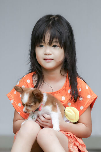 Girl looking away while holding puppy against wall