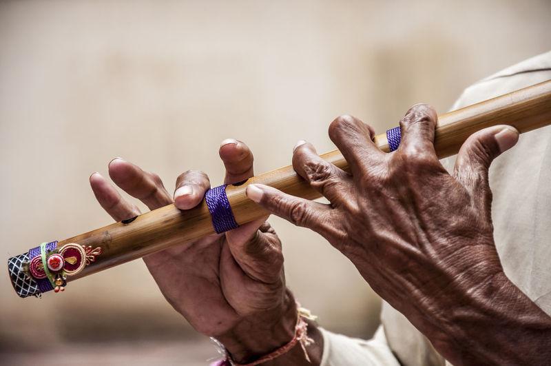 Cropped image of men holding flute