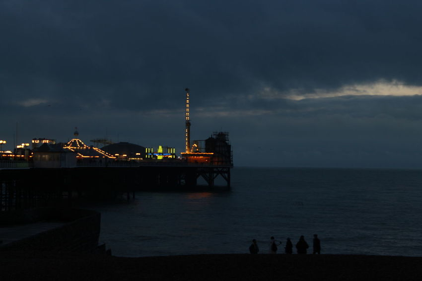 Pier antics. A family watched the sun drop and provided the perfect foreground to an image of the dimly lit promenade. Brighton Pier Beach Cloud - Sky Dusk Horizon Over Water Outdoors Scenics Sea Shadow Sky Sun Sunset Water