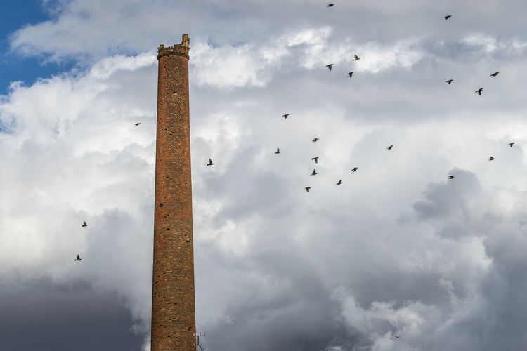 Low angle view of birds flying by damaged tower against cloudy sky