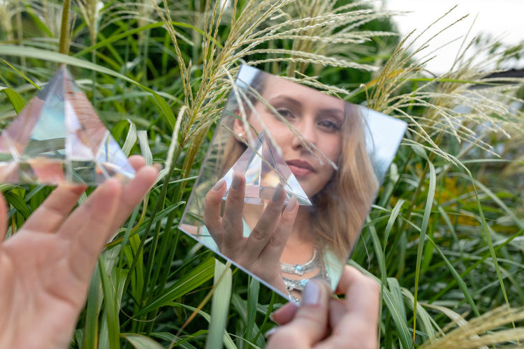 Reflection of woman holding prism in mirror against plants