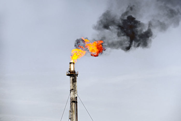 Flaming flare stack against sky