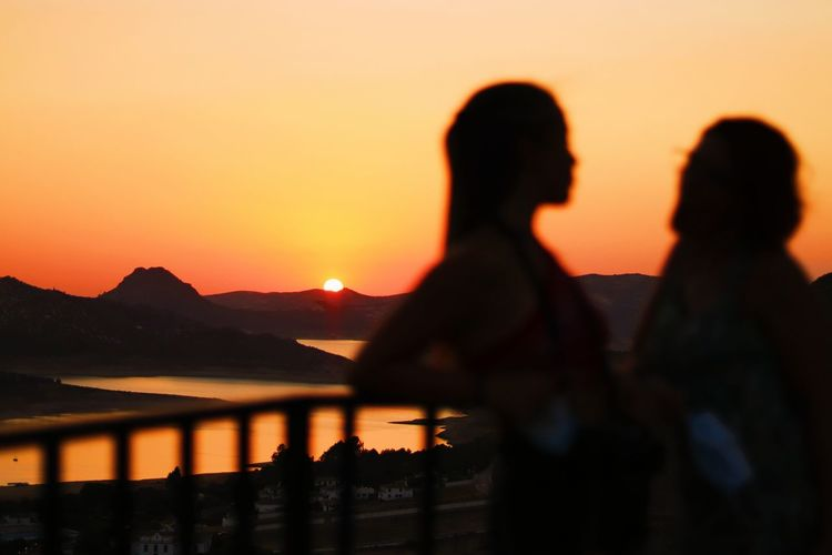 Silhouette people standing by mountain against orange sky during sunset