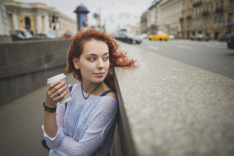 Portrait of young woman drinking coffee in city