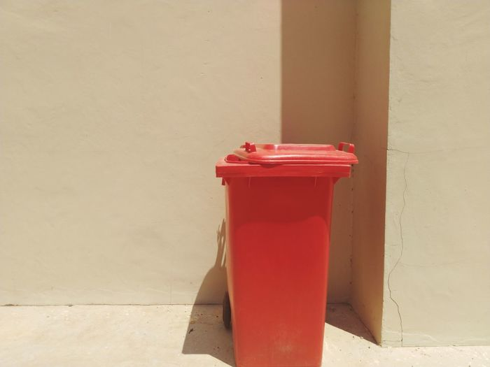 Close-up of red bell on table against wall