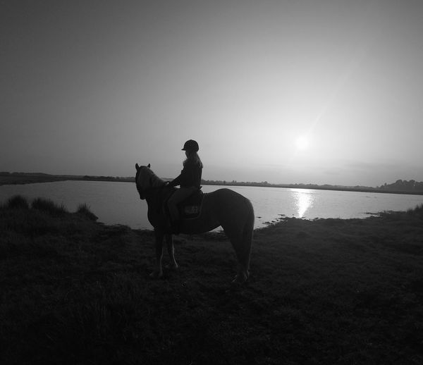 Woman riding horse at riverbank against clear sky